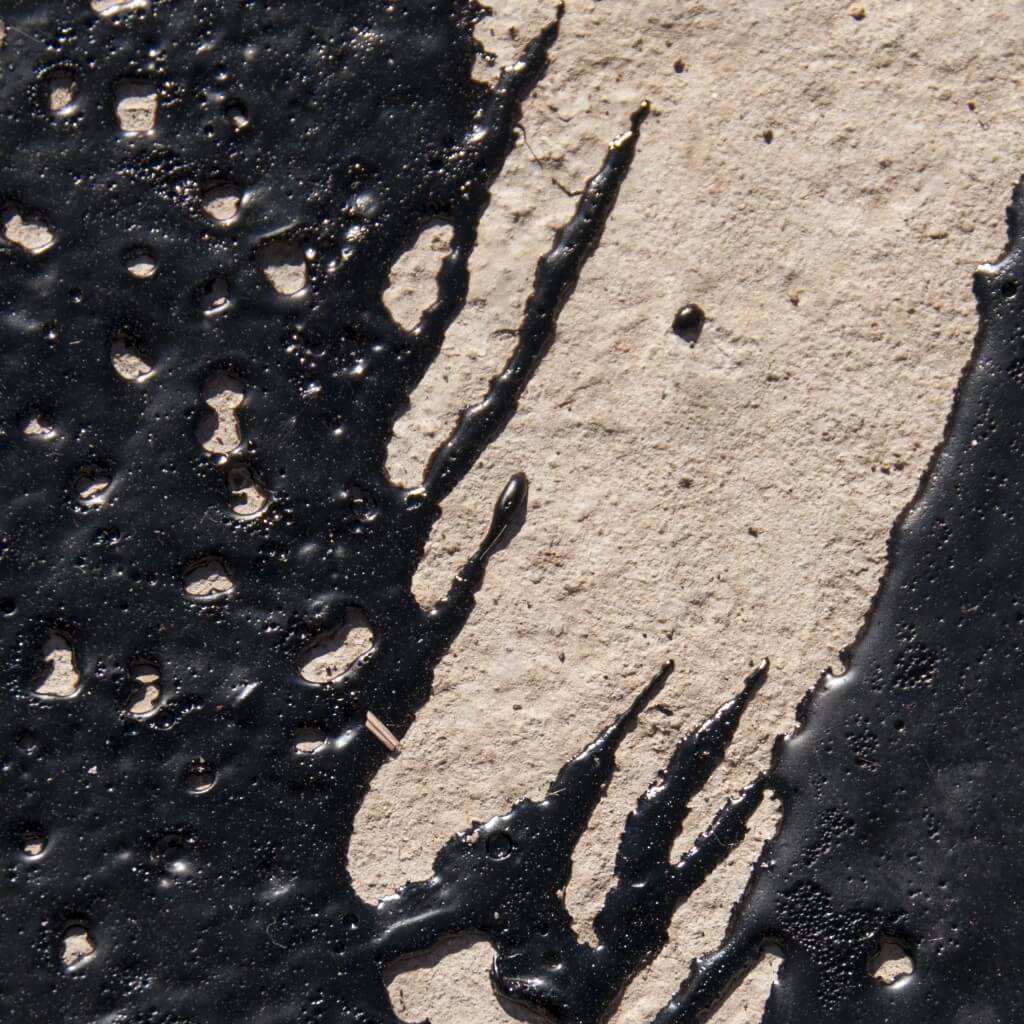 Liquid bitumen applied to concrete bed of footpath during reconstruction in Castlemaine, Victoria, 2009.