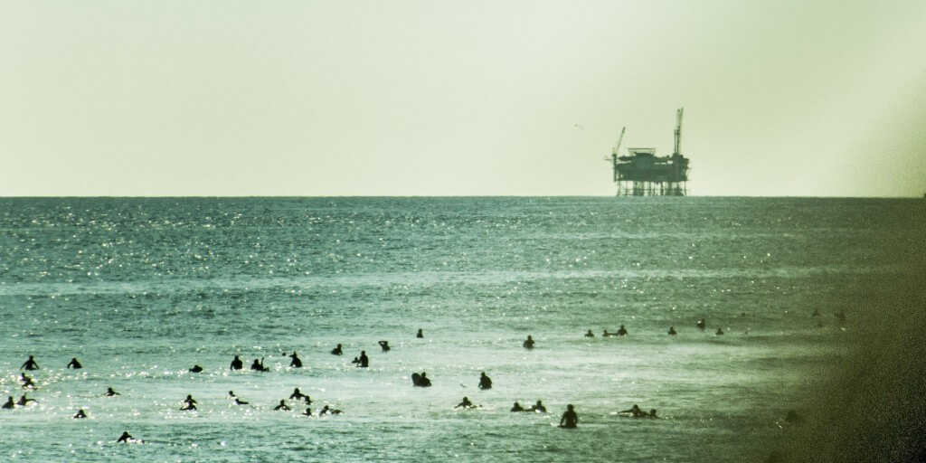 Swimmers near Santa Barbara in-shore form an oil platform. (Shot from moving car.)